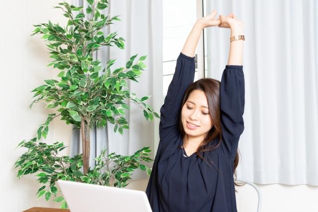 デスクワークの合間に腕を伸ばす女性