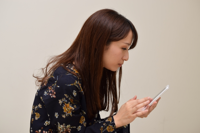 長時間同じ姿勢でスマートフォンを操作する女性