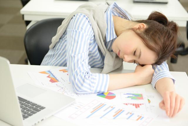 疲労と眠気で仕事がはかどらない女性