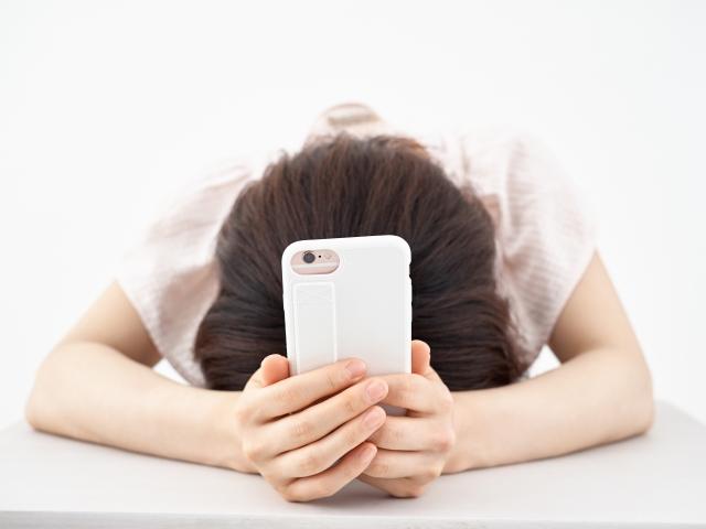 長時間のスマートフォン使用により疲労困憊な女性