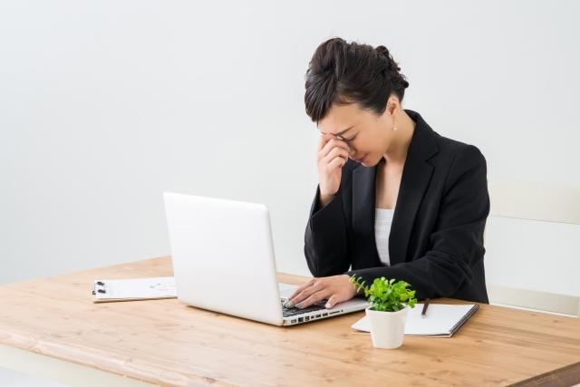 パソコンの凝視で眼精疲労に悩む女性