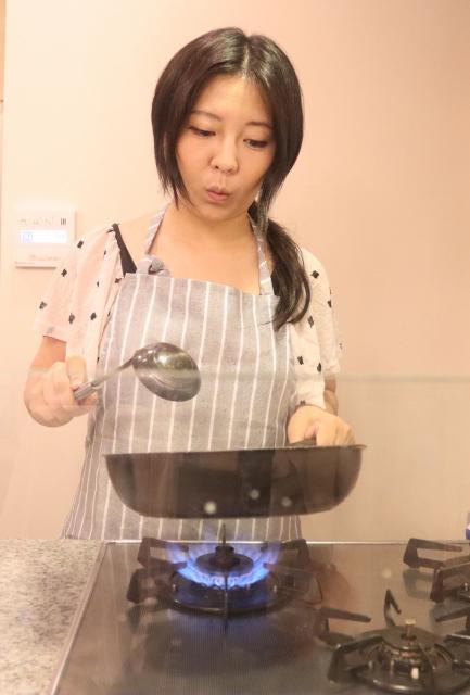 片手でフライパンを持って料理をする女性