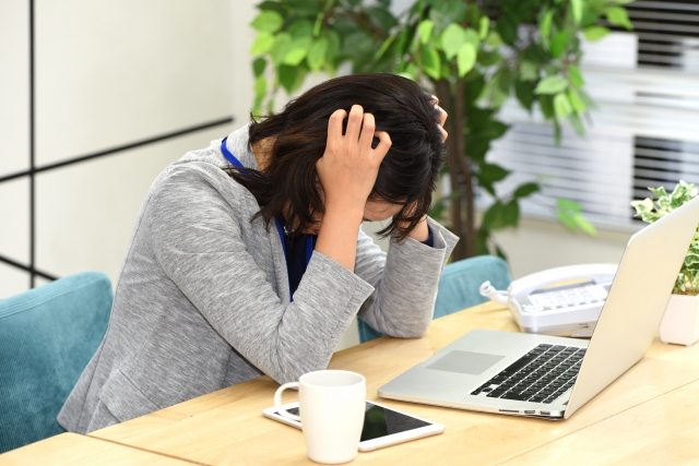 仕事中に頭痛で悩む女性