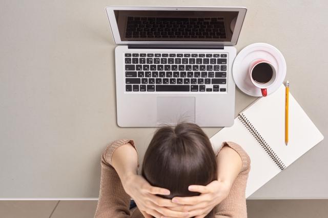 デスクワーク中に頭痛に悩まされる女性