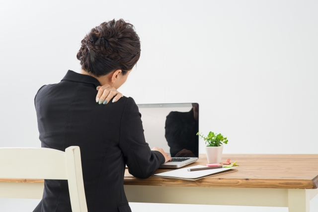 デスクワークによる肩こりに悩む女性