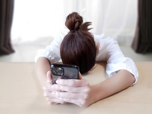 スマートフォンの凝視で眼精疲労に悩む女性