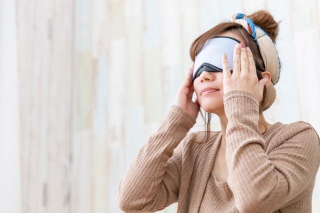 アイマスクで眼を温める女性