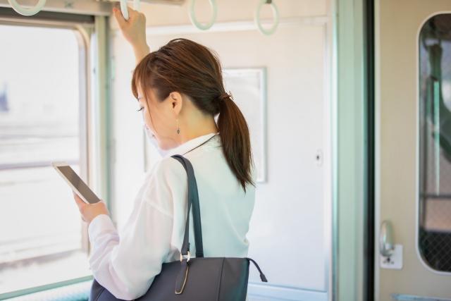 電車内でスマートフォンを操作する女性