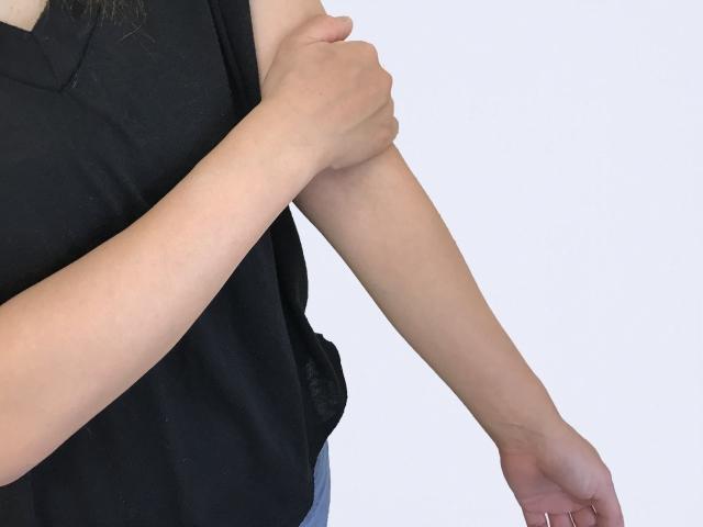 腕の痺れに悩む女性