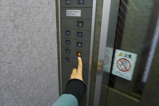 エレベーターのボタンを押す指