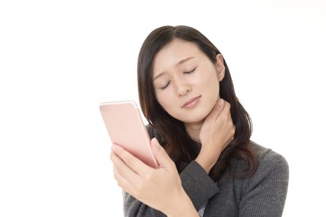 スマートフォンの長時間使用で首こりに悩む女性
