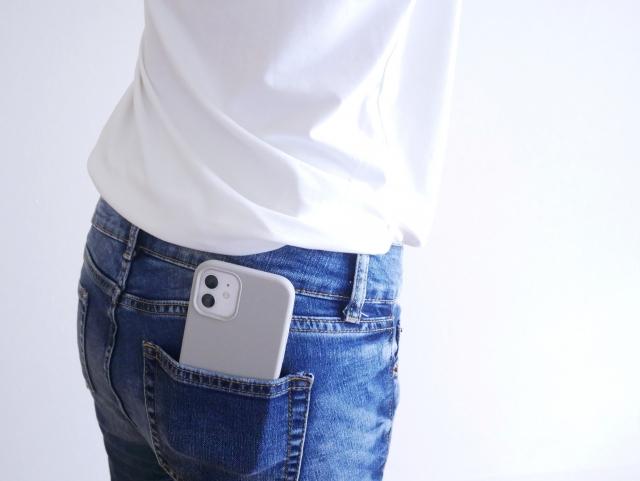スマートフォンをポケットに入れて歩く女性