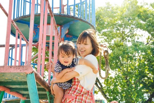 炎天下の下、外で園児と遊ぶ幼稚園の先生