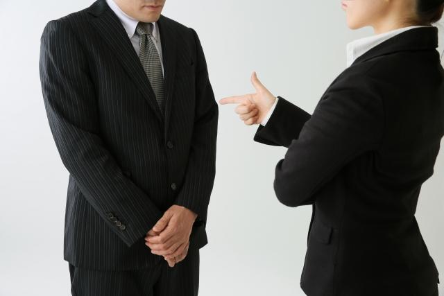 仕事のミスをして上司に叱られる男性社員